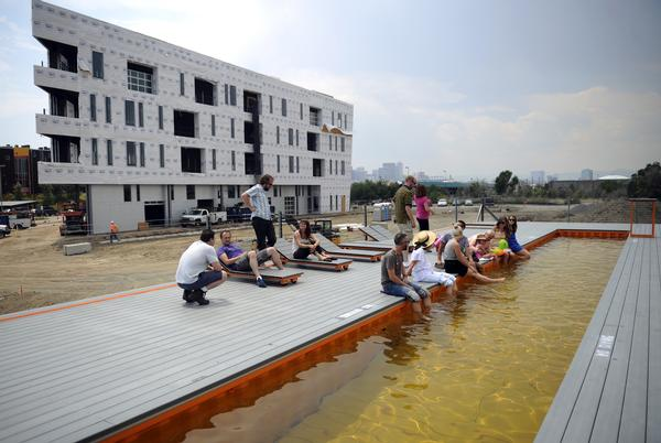 The swimming pool at the TAXI development in Denver is made from two shipping containers welded together. Residents and employees at the development gather on a 100 degree day on the deck around the lap pool on Friday, June 29, 2012. Cyrus McCrimmon, The Denver Post